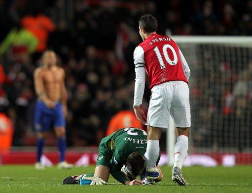 Arsenal goalkeeper Wojciech Szczesny (left) kisses the boot of team mate Robin van Persie after the